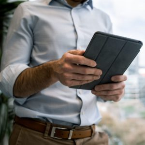 Ein Mann nutzt mit einem Tablet eine mit Microsoft Power Apps erstellte Anwendung. Bild: Unsplash/Tyler Franta