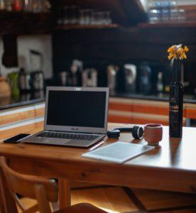 Zu sehen ist eine Küche. am Küchentisch hat jemand wegen der Pflicht zum Home Office seinen provisorischen Arbeitsplatz eingerichtet. Bild: Unsplash/Ben Mysc