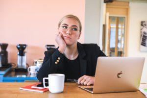 Eine Frau sitzt genervt im Home Office am Küchentisch. Sie ist kein Fan davon, aber muss die Pflicht zum Home Office für Arbeitnehmer einhalten. Bild: Unsplash/magnet.me