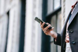 Zu sehen ist der Torso einer Person; eine Hand hält ein Smartphone so, dass die Person es nutzen und dabei in Zukunft auf 6G zurückgreifen kann. Bild: Pexels/Ono Kosuki