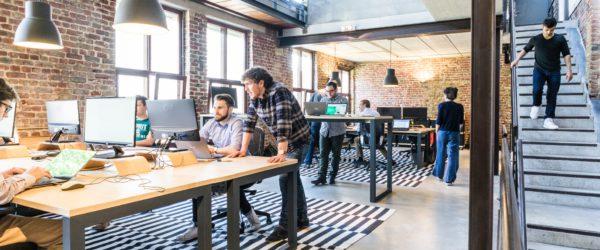 Zu sehen ist ein Büro mit mehreren PC-Arbeitsplätzen und Mitarbeitern. Sie fragen sich: Was ist ein IT-Systemhaus?