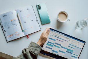 Blick von oben auf einen Tisch mit Arbeitsszene. Eine Person hält ein Tablet, auf dem der Outlook-Kalender geöffnet ist. Cyberkriminelle versenden aktuell falsche Outlook-Termineinladungen. Bild: Unsplash/Windows