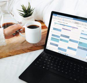 Frühstücksszene; eine Hand hält einen Kaffee, der Laptop ist an, darauf ist der Outlook-Kalender aufgerufen. Ob hier eine falsche Outlook-Termineinladung eingelaufen ist? Bild: Unsplash/Windows