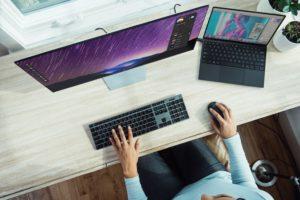 Zu sehen ist aus der Vogelperspektive ein PC-Arbeitsplatz mit Laptop, Monitor, Tastatur und Maus, an dem eine Frau arbeitet. Der Laptop kann Ziel eines Firmware-Angriffs werden. Bild: Unsplash/XPS