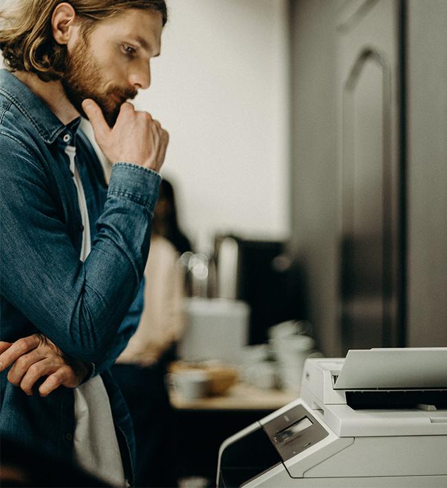 Ein Mann steht am Multifunktionsdrucker und wartet auf ein Fax. Bild: Pexels/cottonbro
