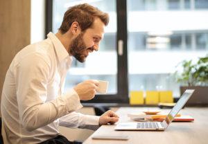 Ein Mann sitzt mit einem Kaffee in der Hand am Laptop, während ein IT-Fachmann per Fernwartung ein PC-Problem löst. Bild: Pexels/Andrea Piacquadio
