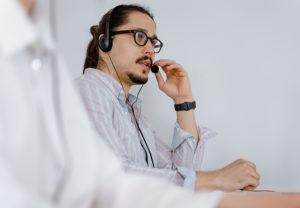 Ein IT-Experte trägt ein Headset und spricht während der Fernwartung mit dem PC-Nutzer. Bild: Pexels/Mart Production