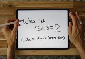 Zwischen zwei Händen liegt ein Tablet, mit einem Stift wurde darauf geschrieben: Was ist SASE? Bild: Unsplash/Kelly Sikkema/IT-SERVICE.NETWORK