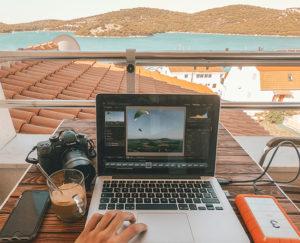 Eine Person arbeitet auf einem Balkon an einem fremden Ort an seinem Laptop – dank Workation-Konzept. Bild: Unsplash/Kornél Máhl