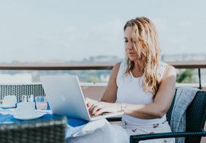 Eine Frau sitzt in einer Urlaubszene am Laptop und arbeitet. Sie nutzt das Workation-Konzept. Bild: Unsplash/Persnickety Prints