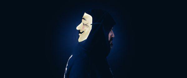 In der Mitte des dunklen Bildes ist ein Mann von der Seite zu sehen; auf dem Hinterkopf trägt er eine Maske. Ist er ein Man-in-the-Middle? Bild: Unsplash/benjamin lehman