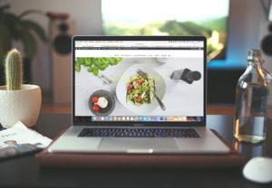 Ein MacBook steht auf einem Küchentisch, darauf ist der Safari-Browser aufgerufen. Bild: Unsplash/Igor Miske