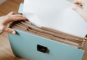 Zu sehen ist eine Aktenmatte mit verschiedenen Fächern, eine Person sortiert ein Papier ein. Sie nutzt die Datenklassifizierung. Bild: Pexels/Anete Lusina