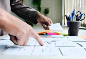 Die Hände einer Person sortieren Notizzettel. Die Person plant die Datenklassifizierung. Bild: Unsplash/UX Indonesia