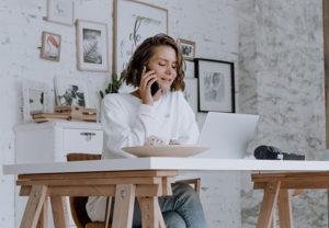 Eine Frau sitzt vor ihrem Laptop am Schreibtisch und telefoniert mit dem Handy. Ob sie eine Home-Office-Zulage bekommt? Bild: Pexels/cottonbro