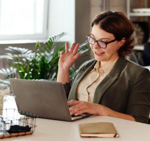 Eine Frau winkt bei einer beginnenden Videokonferenz in die Kamera ihres Laptops. Sie nutzt Live-Untertitel. Bild: Pexels/Marcus Aurelius