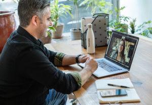Ein Mann sitzt vor seinem Laptop und ist in einem Videomeeting mit einer Geschäftspartnerin. Dank Live-Untertitel klappt die Verständigung in einer Fremdsprache. Bild: Unsplash/LinkedIn Sales Solutions