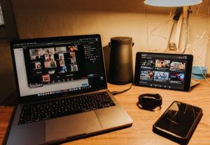 Zu sehen ist ein Schreibtisch mit Laptop und Tablet; darauf läuft ein Zoom-Meeting. Zoom bietet Live-Untertitel auf Englisch. Bild: Unsplash/Gabriel Benois