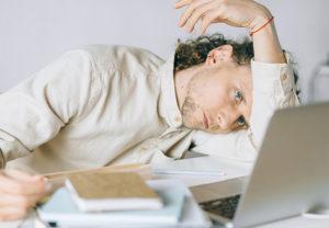 Ein Mann liegt gelangweilt halb auf dem Tisch vor seinem Laptop und wartet darauf, dass die Netzwerkprobleme behoben werden. Bild: Pexels/Nataliya Vaitkevich