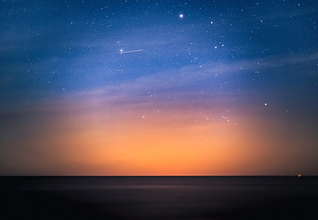 Zu sehen ist ein Abendhimmel; wie Perlen auf einer Schnur reihen sich Satelliten aneinander. Was bedeutet Starlink für Unternehmen? Bild: Unsplash/Marek Piwnicki