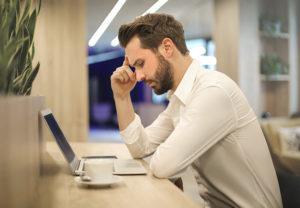 Ein Mann sitzt gequält vor dem Laptop; die dreifache Erpressung hat sein Unternehmen ereilt. Bild: Pexels/Andrea Piacquadio