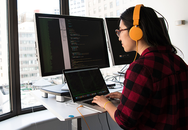 Zu sehen ist eine Frau, die an einem höhenverstellbaren Schreibtisch arbeitet. Sie nutzt ein Tool zur Anomalie-Erkennung. Bild: Pexels/Christina Morillo