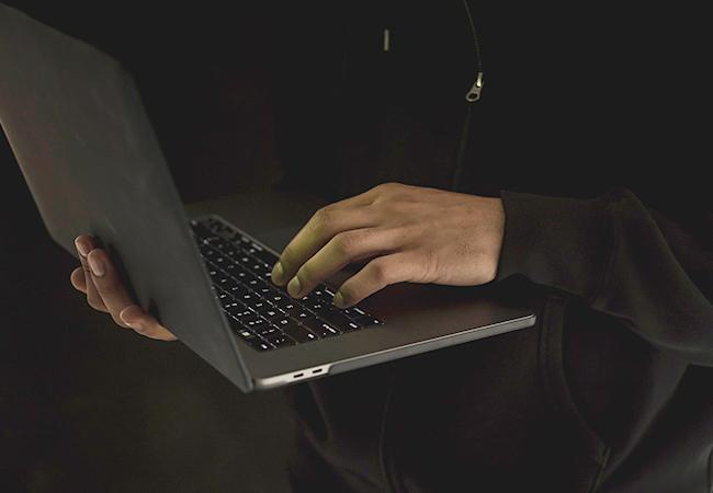 In einer dunklen Umgebung hält eine Person in dunkler Kleidung einen Laptop. Der Cyberangriff wird durch die Anomalie-Erkennung erschwert. Bild: Pexels/Sora Shimazaki