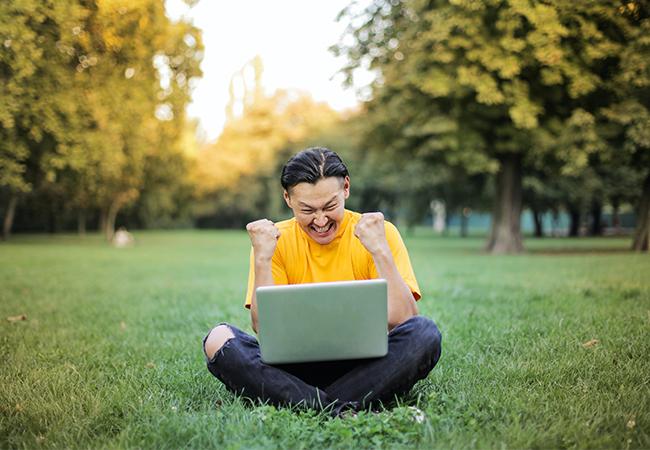 Ein Mann sitzt im Schneidersitz im Park und hat einen geöffneten Laptop auf dem Schoß. Er zeigt mit einer Geste seine Freude – vielleicht über den Erfolg der Initiative Green It. Bild: Pexels/Andrea Piacquadio