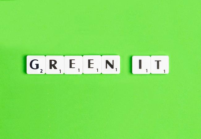 Zu sehen ist der Begriff Green IT aus Scrabble-Buchstaben vor neongrünem Hintergrund. Bild: Unsplash/Edward Howell/Montage IT-SERVICE.NETWORK
