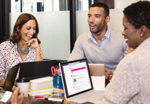 Ein Kollege und zwei Kolleginnen sitzen an einer Tischgruppe und unterhalten sich bei der Arbeit mit Office 2021. Bild: Microsoft