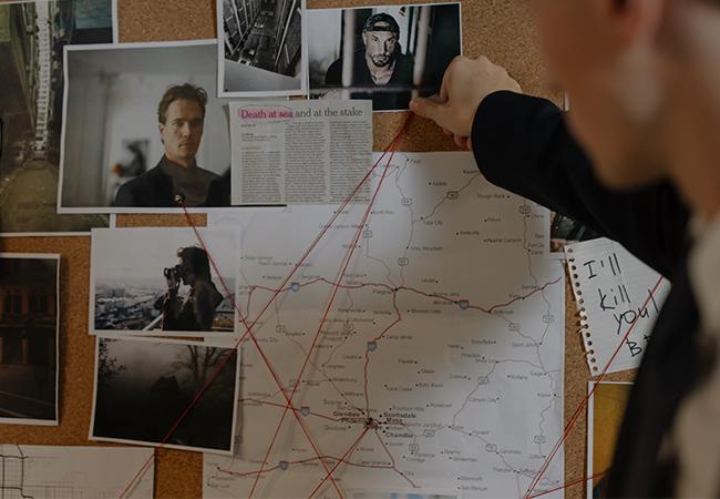 Ein Mann versucht mit Hinweisen an einer Pinnwand ein Verbrechen zu lösen. Die Pegasus-Software kann bei der Strafverfolgung helfen. Bild: Pexels/cottonbro
