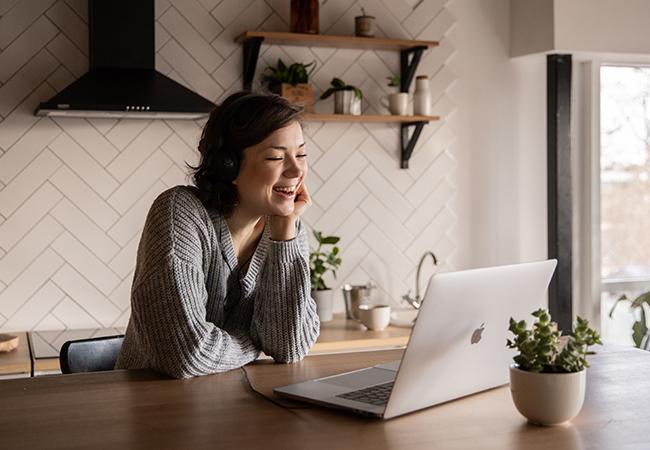 Eine Frau sitzt am Laptop am Küchenthresen und nimmt an einer Videokonferenz teil. Sie nutzt die Untertitelung. Bild: Pexels/EKATERINA BOLOVTSOVA