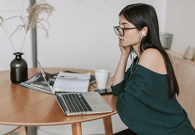 Eine Frau sitzt am Laptop und denkt über eine elegante Abwesenheitsnotiz nach. Bild: Pexels/Vlada Karpovich