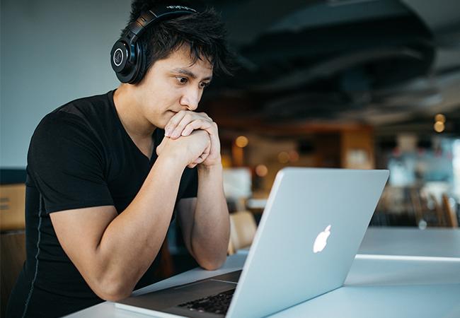 Ein Mann sitzt am Laptop und denkt über eine elegante Abwesenheitsnotiz nach. Bild: Unsplash/Wes Hicks