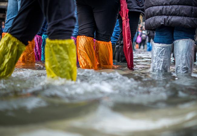 Zu sehen sind Beine, die in Plastiktüten stecken und durch Hochwasser waten. Cell Broadcast soll davor warnen. Unsplash Jonathan Ford