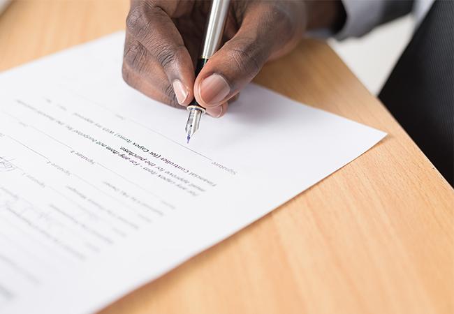 Zu sehen ist eine Hand, die mit einem Kulli ein Dokument unterzeichnet. Jetzt gibt es die elektronische Signatur. Bild: Unsplash/Cytonn Photography