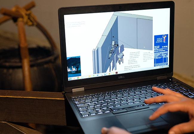 Zu sehen ist ein Laptop, zwei Hände bedienen ihn, darauf ist ein Modell eines Raumes zu sehen; ein digitaler Zwilling ist auch für Gebäude möglich. Bild: Pexels/ThisIsEngineering