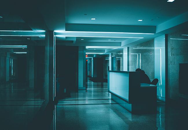 Zu sehen ist der Empfangstresen eines Krankenhauses in einem bläulich-dunklen Licht. Ist es ein digitaler Zwilling? Bild: Unsplash/Brandon Holmes