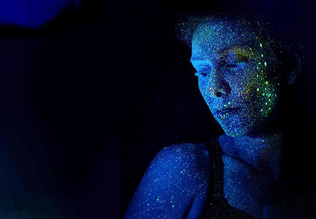 Zu sehen ist eine Frau im Profil mit leuchtenden Neon-Farben, die sie wie einen Avatar erscheinen lassen. Bild: Unsplash/h heyerlein