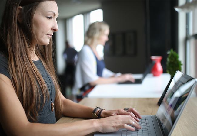 Zwei Frauen arbeiten an ihren Laptops. Nach Least Privilege haben sie unterschiedliche Zugriffsrechte. Bild: Unsplash/TheStandingDesk.com