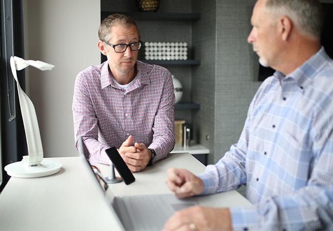 Zwei Kollegen stehen mit ernsten Gesichtern an einem Steh-Schreibtisch. Unzufriedenheit kann zu Sabotage durch Mitarbeiter führen. Bild: Unsplash/TheStandingDesk.com