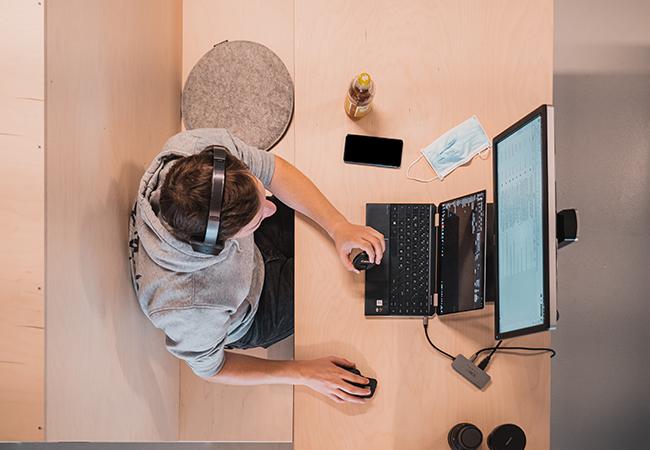 Aus der Vogelperspektive ist eine Person an Laptop und Monitor zu sehen. Ob die Person Opfer von Spoofing wird? Bild: Unsplash/THE 9TH Coworking