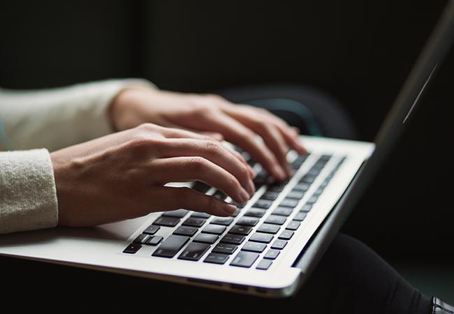 Zu sehen sind Hände auf einer Laptop-Tastatur. Cyber-Attacken und Sabotage in Unternehmen sind eine große Gefahr. Bild: Unsplash/Kaitlyn Baker