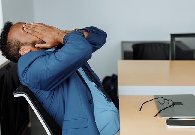 Ein Mann lehnt sich lustlos in seinem Stuhl zurück, die Hände vor das Gesicht geschlagen. Sein Laptop ist geschlossen auf dem Tisch. Es fehlt ihm an Motivation. Vielleicht kann silent Coworking helfen. Bild: Pexels/Thirdman