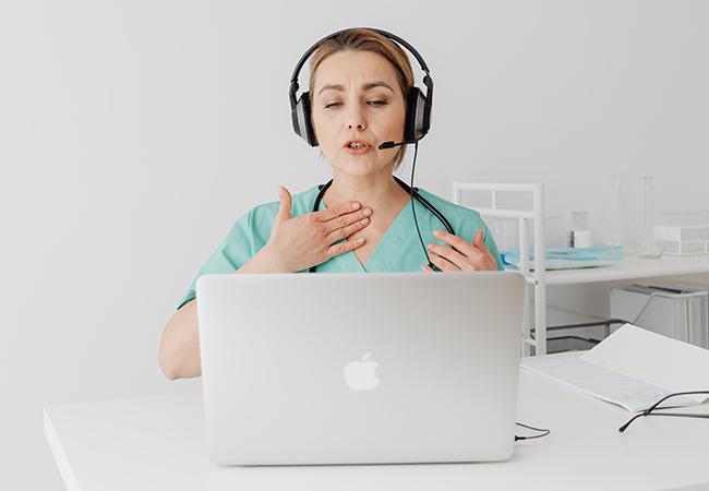 Eine Ärztin sitzt in einer Videosprechstunde und stellt danach möglicherweise eine elektronische Arbeitsunfähigkeitsbescheinigung aus. Bild: Pexels/Karolina Grabowska