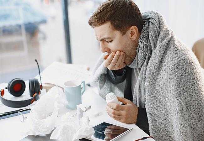 Ein junger Mann sitzt vor seinem Arbeitsplatz, mit Taschentüchern, Medikamenten und dicker Decke. Er will sich beim Arzt eine elektronische Arbeitsunfähigkeitsbescheinigung holen. Bild: Pexels/Karolina Grabowska