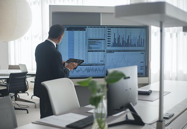 Ein Mann steht vor einem digitalen Whiteboard mit zahlreichen Daten. Die 3-2-1-Regel stellt deren Verfügbarkeit sicher. Bild: Pexels/Kampus Production