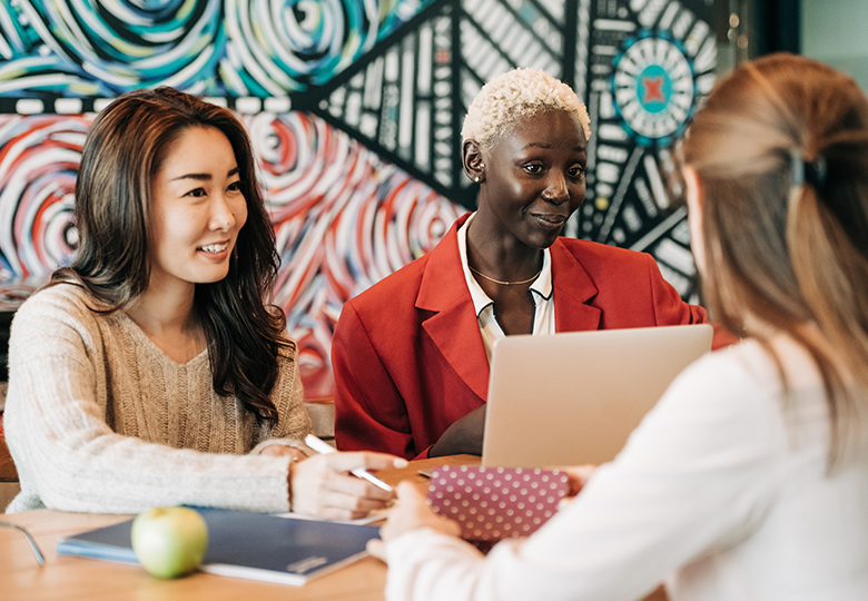 Drei Kolleginnen arbeiten an einem Tisch zusammen, eine Frau hat einen Apfel. Obst gehört in der Firma zu den Benefits für Mitarbeiter. Bild: Pexels/Alexander Suhorucov