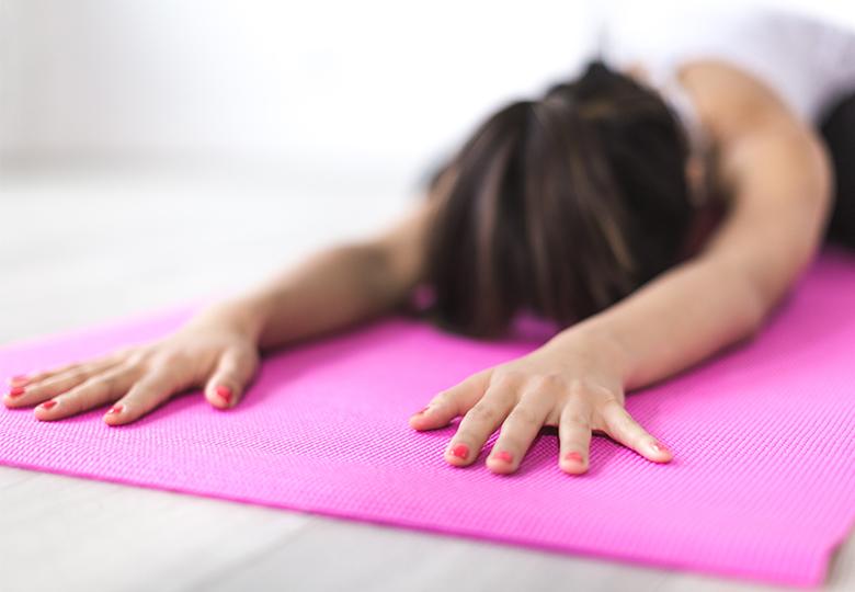 Eine Frau macht auf einer Matte Yoga in der Mittagspause. Das Angebot gehört zu den Benefits für Mitarbeiter. Bild: Pexels/Burst