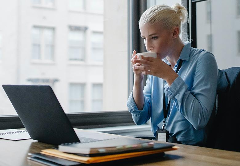 Eine Frau sitzt an ihrem Arbeitsplatz am Laptop und trinkt einen Kaffee. Gelten kostenlose Getränke als Benefits für Mitarbeiter? Bild: Pexels/Sora Shimazaki